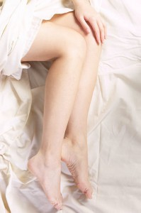 Woman s legs in bed sheets uid